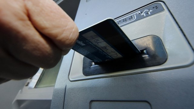 A person inserts a debit card into an ATM machine