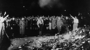 German soldiers and civilians give the Nazi salute as they burn books in May 1933