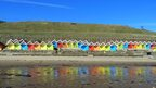 Colourful beach huts, a hill and clear blue sky behind.