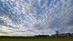 A blanket of mackerel cloud over a cricket field.