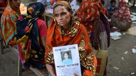 The mother of a woman who worked inside Rana Plaza holds up a picture of her (9 May 2013)