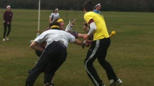 Two players try to grab a tag from the clothes of a man dressed in yellow