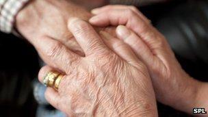 Carer holding elderly person's hand