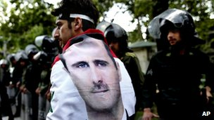 A man wrapped in a Syrian flag with a portrait of President Bashar Assad walks past riot police at an anti-Israeli rally in Tehran, Iran. Photo: 6 May 2013