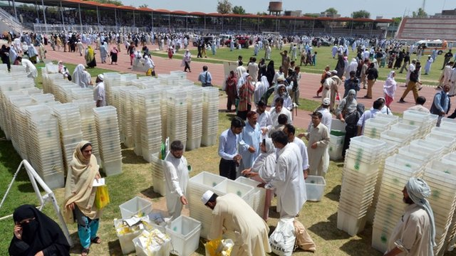 Pakistani election officials receive ballot boxes and other election materials at a distribution centre in Peshawar