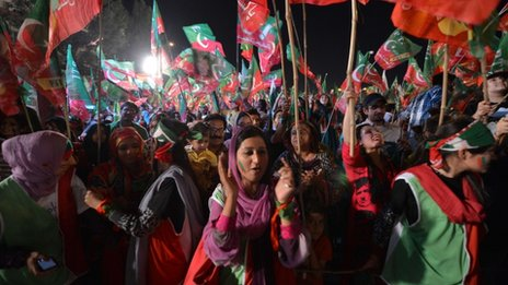 Supporters of Pakistani politician and former cricketer Imran Khan cheer as they wait to listen Khan video link address from a hospital during his last election campaign meeting in Islamabad on May 9, 2013