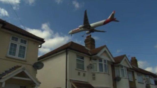 A plane flies over houses near Heathrow Airport