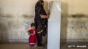 A woman accompanied by her child, casts her vote in Lahore
