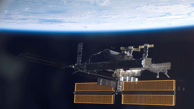 The International Space Station over a blue and white Earth