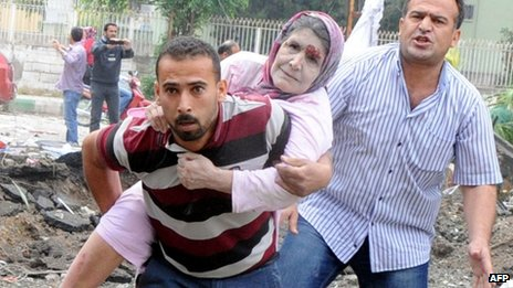 A resident evacuates an injured woman from the bomb scene in Reyhanli, Turkey, 11 May