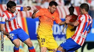 Barca's Lionel Messi (centre) in action against Atletico Madrid