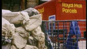 A pile of post bags and a Royal Mail delivery lorry.