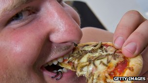 A festival-goers enjoys an 'insects pizza' at one of the many food stalls during the 34th edition of the Paleo festival on July 22, 2009 in Nyon.