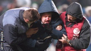 An injured fan is helped by stewards