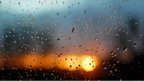 Raindrops on glass. Yellow and blue strips outline sunset. An insect is on the glass.