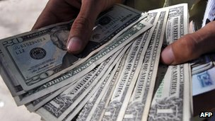 Afghan money changer with dollars (October 2011)