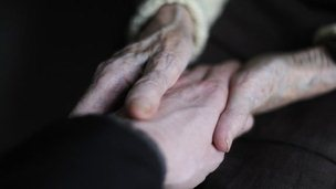 Picture of an elderly patient holding the hand of a man