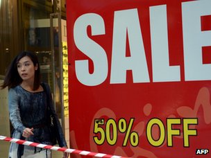 A woman walks past a sale sign in a show window in Sydney
