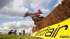 Horse jumping over a racecourse hurdle