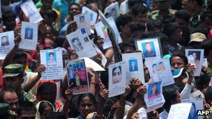 People hold up pictures of their missing relatives in Savar, near Dhaka. Photo: 14 May 2013