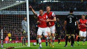 Lukas Podolski celebrates scoring against Wigan