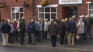 People queuing outside village hall