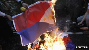 Activists burn Philippine national flags in front of the Manila Economic and Cultural Office, the de facto Philippine embassy in Taiwan, during a protest against the Philippine government in Taipei on 13 May 2013