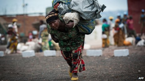 A woman flees fighting in eastern DR Congo on 18 November 2012