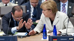 A file picture taken on 21 May, 2012 shows French President Francois Hollande (left) speaking with German Chancellor Angela Merkel during a meeting with partner nations in Chicago