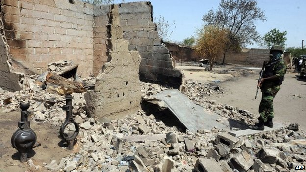 A Nigerian soldiers stands beside a burnt house after the army clashed with Boko Haram insurgents in Borno state. Photo: April 2013