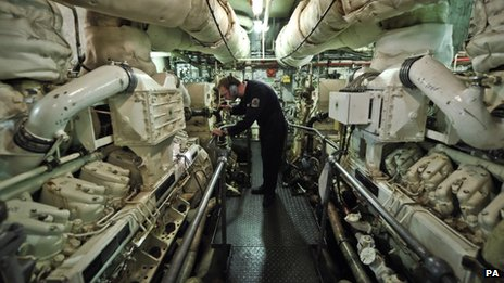 A mechanical engineer checks one of two V16 diesel engines that provide electricity to HMS Edinburgh