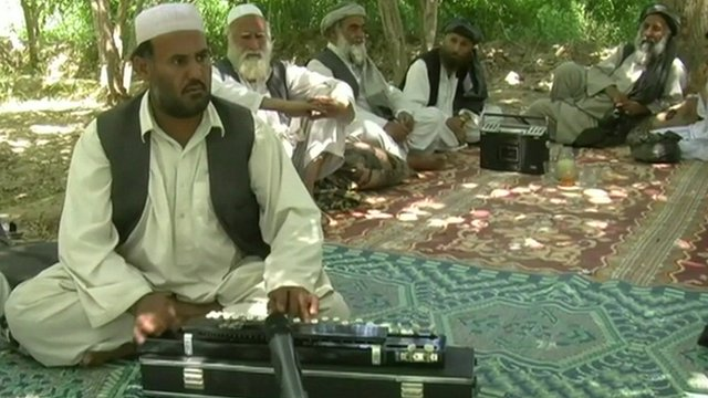 Afghan musician playing a Benjo