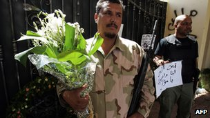 A Libyan security guard carries flowers for Stevens