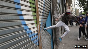 Protester kicks a store's shutter during a rally in Santiago (11 April 2013)