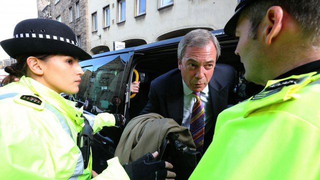Nigel Farage is escorted by police as he exits a taxi as its path was blocked by protesters as he leaves the Cannons Gait pub during his visit to Edinburgh