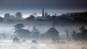 The winter sun begins to rise over mist and fog that has formed over fields on the Somerset Levels