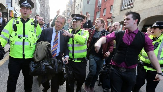 UKIP leader Nigel Farage being escorted by police officers as he leaves the Cannons Gait pub as protestors heckle him