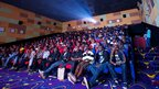 People watch Iron Man in 3D at a cinema in Kigali, Rwanda, on 10 May 2013