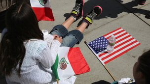 Girl scouts with Mexican and American flags rest after walking in a Cinco de Mayo parade on 4 May 2013 in Denver, Colorado.