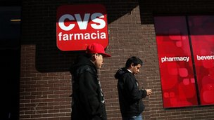 Hispanic residents walk by a bilingual sign for a CVS pharmacy on 28 March  2011 in Union City, New Jersey