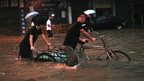 People push a tricycle along a flooded street in Zhuhai, Guangdong province, 8 May 2013