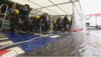 Racers shelter from heavy rain at the NW200