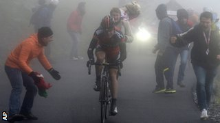 Cadel Evans appears out of the gloom at the end of stage 14
