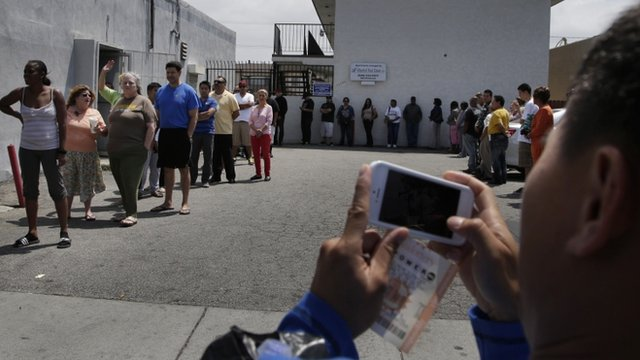 A man takes pictures of people queuing to buy Powerball tickets outside Bluebird liquor store in Hawthorne, California