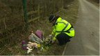 Police officer putting flowers where baby was found