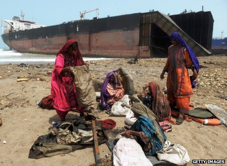 Women collect scrap metal on a beach in Pakistan