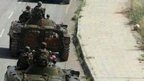 Social media image purportedly shows government tanks moving into  Qusair, Syria, as civilians look on