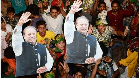 Supporters of former Pakistani Prime Minister and head of the Pakistan Muslim League-N (PML-N), Nawaz Sharif, carry portraits
