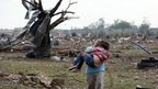 A woman carries a child after the tornado in Moore, Oklahoma (20 May)