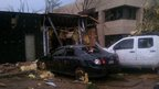 Cars with debris on them and windows smashed in. Building with walls broken away.